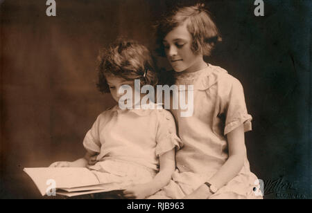 Older girl helps her younger sister read a book - formal studio portrait taken on 17th May 1930. The girls are Vera and her sister Doris Dingley. The photograph was taken at the studio of B Wilkin at Elgin, a Canadian rural community in Albert County, New Brunswick, Canada. - Stock Image