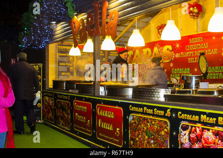 30 November 2018 A busy food stall selling Spanish dishes at the Belfast Christmas Fair located in a wooden booth in the grounds of Belfast City Hall. - Stock Image