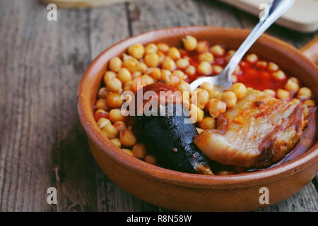 Chickpeas, sausage and bacon in a crockpot by a little metal spoon. Typical food from Madrid, Spain, with a rustic wooden board as a background. - Stock Image