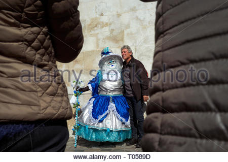 A man poses for photos next to a participant at the Annecy Venetian Carnival. Annecy. Auvergne-Rhone-Alpes, south east France. - Stock Image