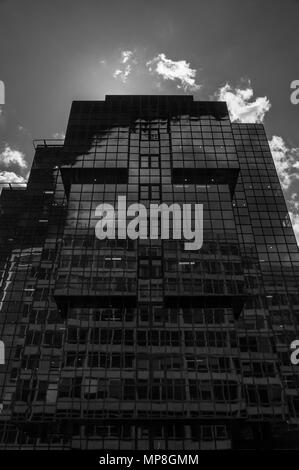 Black and white image looking up at a dark, domineering office building in London - Stock Image
