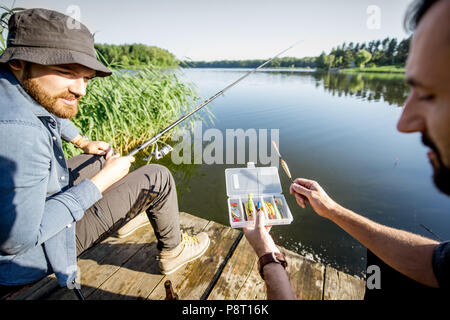 Two men with fishing tackles during the fishing process on the lake in the morning - Stock Image