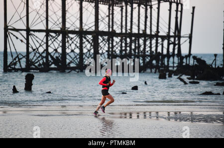 Brighton UK 10th October 2018 - A runner on the beach passes by the West Pier on Brighton seafront during a beautiful sunrise with some areas of the south east expected to reach the mid twenties in temperature today . However storms are forecast to spread across Britain on Friday Credit: Simon Dack/Alamy Live News - Stock Image