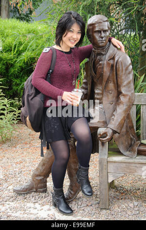 Japanese student sitting on Charles Darwin statue, Christ's College, Cambridge, England, UK - Stock Image