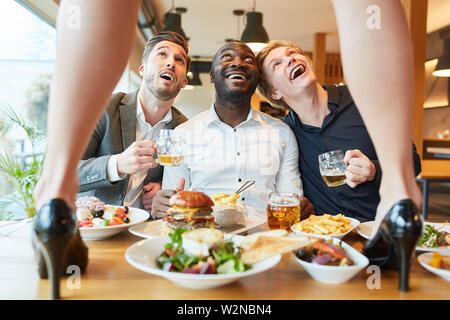 Delighted men admire striptease show at dinner party in the restaurant - Stock Image