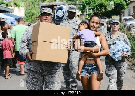 U.S. National Guard soldiers deliver emergency supplies to Puerto Rican residents during relief efforts following - Stock Image