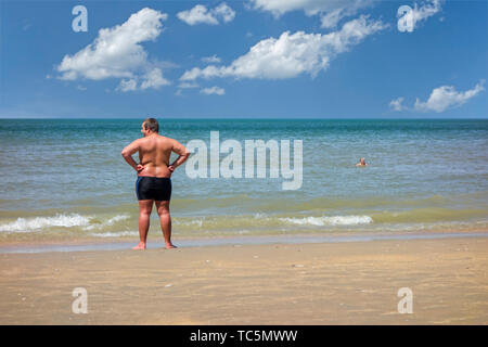 Corpulent / obese young man in swimsuit standing on sandy beach looking over the sea during the summer holidays - Stock Image