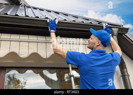man installing house roof rain gutter system - Stock Image