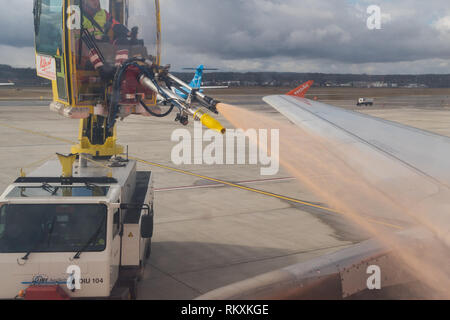 worker de-icing the wings of an easy Jet plane before takeoff - Euroairport - Stock Image