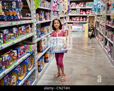 Girl picks toy in store - Stock Image