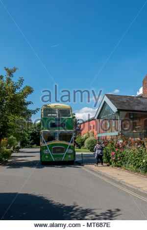 A photographer shoots a wedding couple aboard a restored SouthDown bys in green and cream livery outside the Farnham Maltings, Surrey, UK - Stock Image