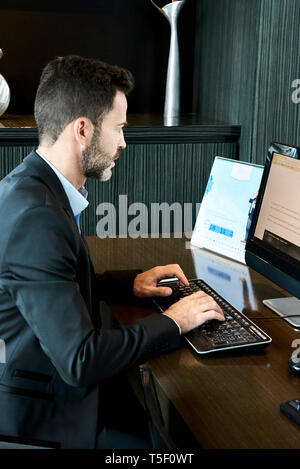 Businessman working on computer in hotel - Stock Image