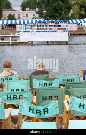 Spectators and empty canvas spectator chair backs labelled with HRR, at Henley Regatta, Henley-on-Thames, Oxfordshire, UK on a cold day - Stock Image