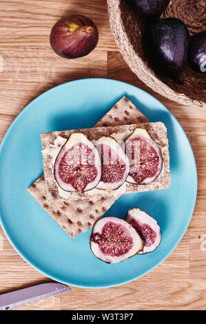 sliced figs on dietetic bread on a plate - Stock Image