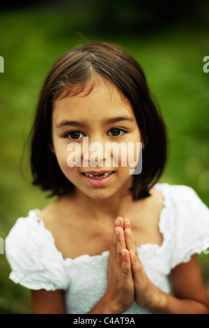 Girl holds hands together - Stock Image