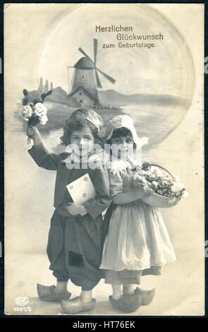 A greeting postcard printed in Germany, shows a boy and a girl with flowers in traditional Dutch clothing: The inscription - Stock Image
