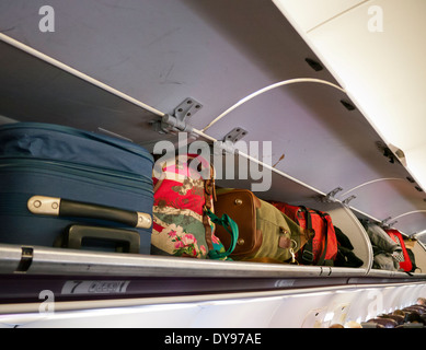 Baggage stored in overhead lockers on a passenger jet - Stock Image