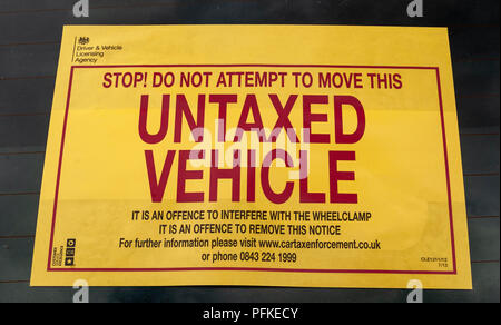 A Untaxed Vehicle notice stuck on the windscreen of a car - Stock Image