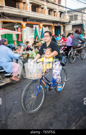 Mae Sot, Thailand - February 3rd 2019: Woman and child cycling through the morning market. Bicycles are widely used in the town. - Stock Image
