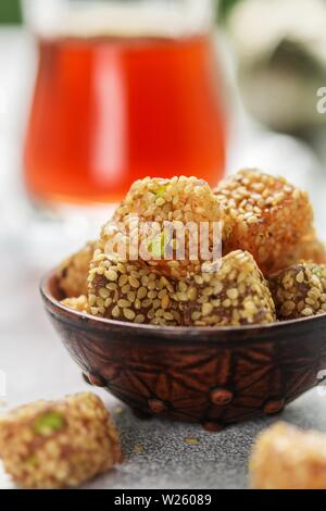 Traditional Turkish delight. lokum. Oriental sweets with sesame and pistachios in a ceramic bowl on the table. A treat for tea. Selective focus - Stock Image