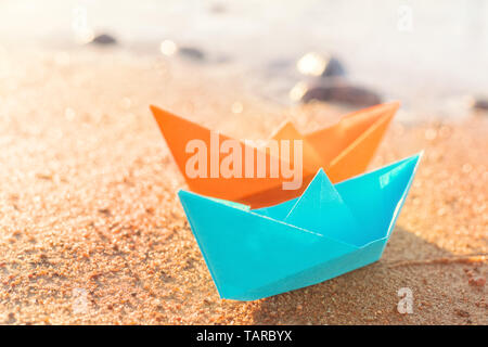 Orange and blue paper boats, blue and orange, on sandy beach outdoors. Selective focus on front - Stock Image