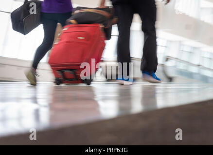 Airport Travelers Walking Through Concourse Low Angle - Stock Image
