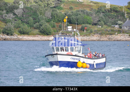 The Osprey, one of the inter island boats on the Isles of Scilly, approaches Bryer after the short journey from Tresco in the background.Cornwall, UK - Stock Image