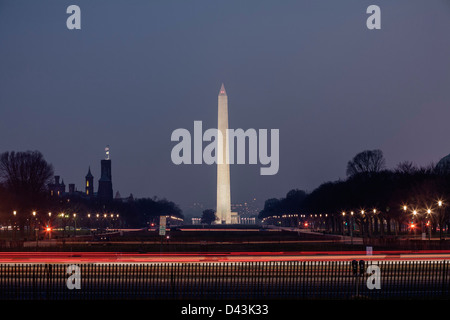 Looking west towards Washington Monument at night with light trails from moving vehicles in the foreground, Washington - Stock Image