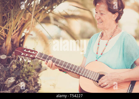 Senior caucasian beautiful cheerful happy lady adult people singing a guitar outdoor enjoying the leisure activity - third age silver society concept  - Stock Image