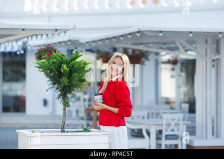 Close-up portrait of magnificent caucasian girl lady wearing red sweater and white skirt. Lovable long-haired blonde woman enjoying life and having fu - Stock Image