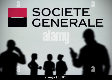 The Societe Generale logo is seen on an LED screen in the background while a silhouetted person uses a smartphone (Editorial use only). - Stock Image