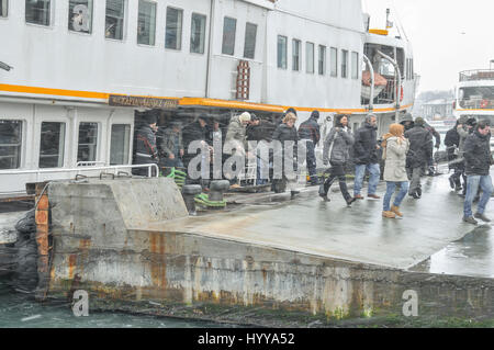 Passengers exit a ferry boat on a cold winter's day, at the Eminönü ferry pier in Istanbul. - Stock Image