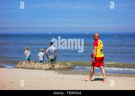 Beach lifeguard walking past father with two children building sand castle at seaside resort along the Belgian North Sea coast, Belgium - Stock Image