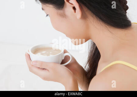 Young woman holding a cup, - Stock Image