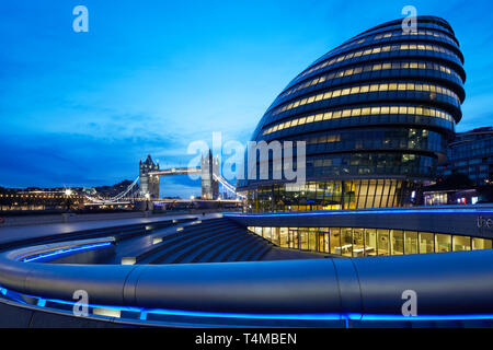 City Hall and Tower Bridge illuminated at sunrise, London, England, Great Britain - Stock Image