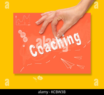 A hand picking up a Coaching concept on a colorful drawing board. - Stock Image