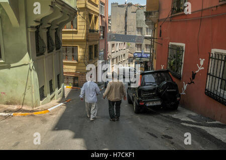 Two men walk on a street lined with old buildings in Istanbul. - Stock Image