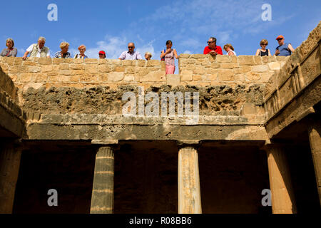 Tourists look into one of the open tombs at Tombs of the Kings, Tombs of the Kings, Paphos, Cyprus October 2018 - Stock Image