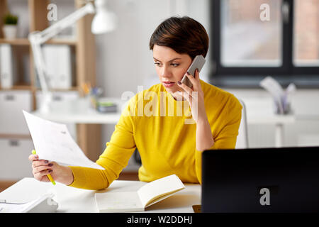 businesswoman calling on smartphone at office - Stock Image