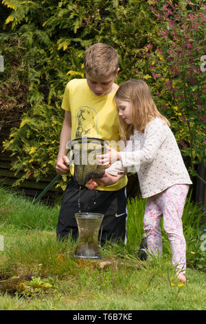 young children, brother and sister, pond dipping together, with net, garden wildlife pond, older brother, younger sister, playing together. nature, - Stock Image