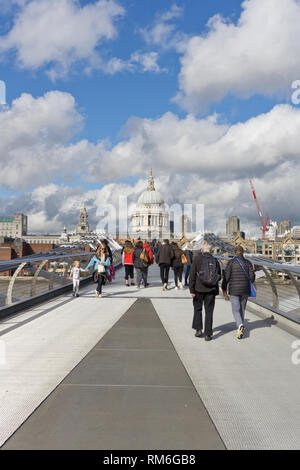 People crossing the Millennium Bridge from the South Bank towards St Paul's Cathedral, London, UK - Stock Image