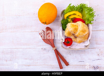 Clean food breakfast croissant and salad on wooden table. - Stock Image