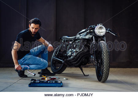 Young male motorcyclist doing maintenance on vintage motorcycle in garage - Stock Image