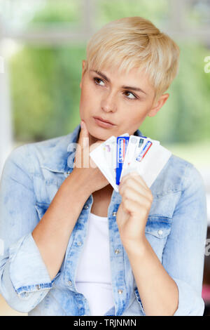 Woman looking concerned holding credit cards - Stock Image
