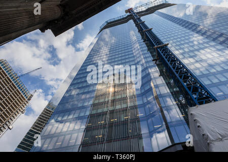 View of partly glazed new skyscraper office block, 22 Bishopsgate, under construction in the City of London financial district EC2 reflecting Tower 42 - Stock Image