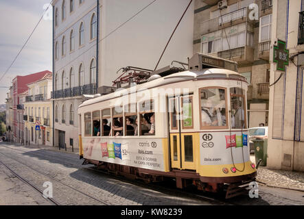 A traditional tram travelling uphill through the central streets of Alfama district Lisbon, Portugal - Stock Image