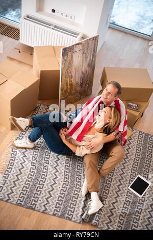 happy smiling couple sitting on fleece blanket on floor at new home - Stock Image