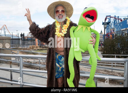 A man in a costume holding a large kermit the frog puppet prior to the annual Polar Bear Club New Year's day swim in Coney Island, NYC. - Stock Image