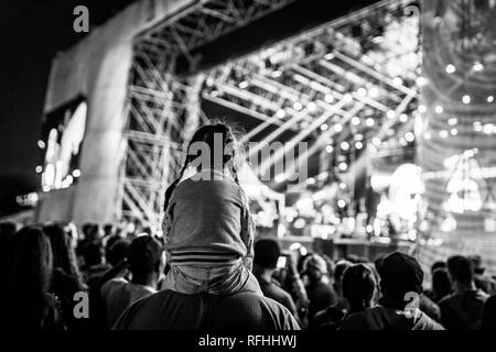 Young girl watching a concert from her dad shoulders, black and white filter applied - Stock Image