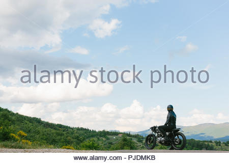 Young male motorcyclist on vintage motorcycle looking out over landscape, Florence, Tuscany, Italy - Stock Image